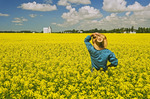 a man looks out over a field of bloom stage canola,  Sanford, Manitoba, Canada