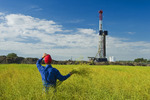 a man looks out over a field of pod stage canola with an oil drilling rig in the background, near Sinclair, Manitoba, Canada