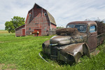 closeup of old truck filled with rusted barbed wire and barn in the background near Bruxelles, Manitoba, Canada