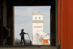 a man holding a shovel looks out over an old grain elevator, Kincaid, Saskatchewan, Canada