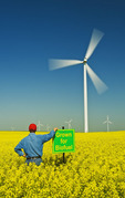 man and biofuel sign in a bloom stage canola field with wind turbines in the background,  near St. Leon, Manitoba, Canada