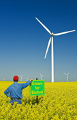 man with a biofuel sign in a bloom stage canola field with wind turbines in the background,  near St. Leon, Manitoba, Canada
