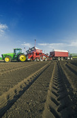 a potato planter is loaded with seed potatoes, near Cypress River, Manitoba, Canada