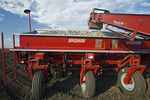 a potato planter is loaded with treated seed potatoes, near Cypress River, Manitoba, Canada
