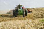moving tractor and air till seeder planting canola in a zero till wheat stubble field, Bruxelles, Manitoba, Canada