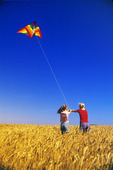 girls flying a kite in spring wheat field