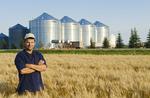 a farmer in his mature wheat, grain bins(silos) in the background,  Lorette, Manitoba, Canada