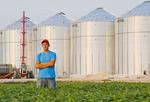 a young man in soybean field, grain bins(silos) in the background,  Lorette, Manitoba, Canada