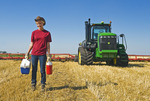 farm girl in a field of grain stubble with tractor and cultivating equipment in the background, Tiger Hills area, Manitoba, Canada