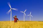 a girl in a wind-blown mature wheat field with wind turbines in the background, near St. Leon, Manitoba, Canada