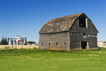 hay roll and old barn with grain elevator in the background, Cypress River, Manitoba, Canada