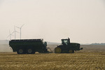 female tractor operator and grian wagon during the spring wheat harvest, near Somerset, Manitoba, Canada