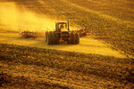tractor pulling cultivating equipment, near Lorette, Manitoba, Canada