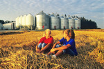 children relaxing on wheat swath  Manitoba, Canada (model released)