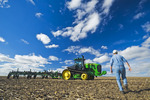 motion study of a farmer walking in a cultivated field containing corn resudue, towads his tractor and cultivating equipment, Tiger Hills area, Manitoba, Canada