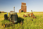 old tractors with grain elevator in the background, abandoned town of Bents, Saskatchewan, Canada