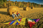 boys relaxing next to a round straw bale after kite flying, near Oakbank, Manitoba, Canada (model released)