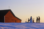 a family make a snowman in front of a red barn, near Glass, Manitoba, Canada