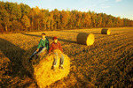 children relaxing on round straw bale