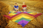 children relaxing on wheat swath after kite flying,