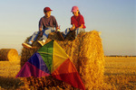 children relaxing on round straw bale after kite flying