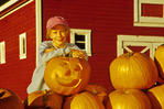 children  holding jack-o-lantern next to pumpkins