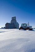 old tractor with old grain elevator in the background, Benson, Saskatchewan, Canada