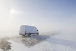 van on road covered with blowing snow, near Morris, Manitoba, Canada