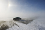 car on road covered with blowing snow, near Morris, Manitoba, Canada