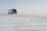 truck on road covered with blowing snow, near Morris, Manitoba, Canada