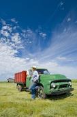 man beside old farm truck, near Ponteix,  ,Saskatchewan, Canada