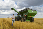 a young farmer in durum wheat stubble , grain wagon and farm truck in the background, near Ponteix, Saskatchewan, Canada