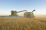 a combine unloads barley into a grain wagon on the go near Ponteix,  Saskatchewan, Canada