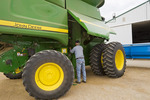 a farmer adjusts belts on a combine parked in his farmyard, near Ponteix, Saskatchewan, Canada