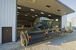 a  combine parked front of a farm repair shop, near Lorette, Manitoba, Canada
