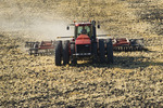 a tractor with a cultivater work soil containing wheat stubble. near Lorette, Manitoba, Canada