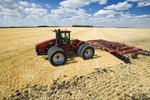 a tractor with a disc harrow works soil containing barley stubble. near Lorette, Manitoba, Canada