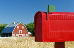 closeup of rural mailbox with red barn and spring wheat field in the background, Grande Pointe, Manitoba, Canada
