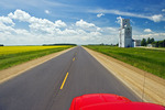 road going across the prairies with grain elevator in the background, near Culross, Manitoba, Canada