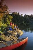 family relaxing along shoreline, boy fishing, Big Whiteshell Lake, Whiteshell Provincial Park, Manitoba, Canada