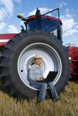farm girl using laptop computer while sitting on tractor wheel, near Dugald, manitoba, Canada (MR)