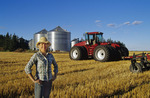 farm girl near tractor with cultivating equipment, spring wheat stubble in field, near Dugald, Manitoba
