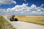 a tractor with cultivating equipment on a country road, stacked wheat straw bales in the background, near Winnipeg, Manitoba ,Canada