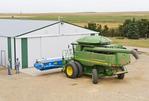 a combine parked front of the farm repair shop, near Ponteix, Saskatchewan, Canada