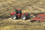 a tractor with a disker works soil containing wheat stubble. near Lorette, Manitoba, Canada