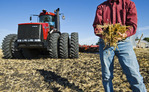 close-up of man holding soil and wheat stubble with tractor pulling cultivating equipment and grain storage bins in the background, near Lorette, Manitoba, Canada