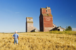 barley field and grain elevators, abandoned town of Lepine, Saskatchewan, Canada