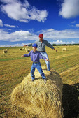 father and son play on a round hay bale near Winnipeg, Manitoba, Canada