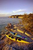 couple with kayak along limestone cliffs, Steep Rock, along Lake Manitoba, Canada