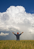 a man looks out over a barley field with a cumulonimbus supercell cloud mass in the background near Bromhead, Saskatchewan, Canada